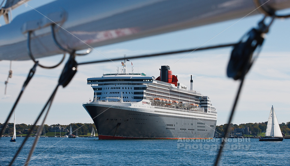 The cruise liner see from under the boom of a local sailboat