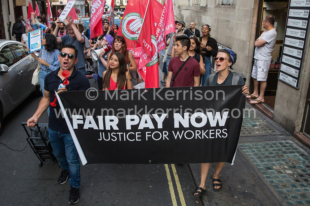 London, UK. 12 July, 2019. Members of the Cleaners and Facilities Branch of the IWGB (Independent Workers of Great Britain) trade union protest in the streets around 5 Hertford Street in Mayfair, which also houses exclusive private club Loulou's, to call for its kitchen porters, recently outsourced through ACT Clean, to be paid the London Living Wage and given terms and conditions including suitable sick pay, holidays and pension contributions. Numerous unmarked security guards were present outside the venue.