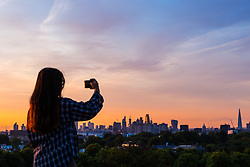 London, August 16 2017 . A woman photographs the city skyline as London wakes up to a glorious sunrise. © Paul Davey.