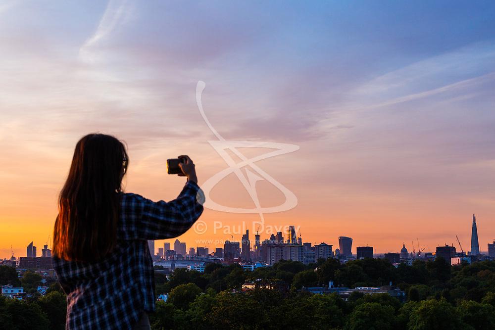 London, August 16 2017 . A woman photographs the city skyline as London wakes up to a glorious sunrise. © Paul Davey.