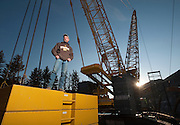 """PRICE CHAMBERS / JACKSON HOLE NEWS&GUIDE<br /> Scotty Fowden stands atop thousands of pounds of steel counterweight that helps keep the Kobelco SL6000 crawler crane from tipping over into the Snake River. The massive crane has a maximum lift capacity of 600 tons, which comes in handy when lowering giant steel beams into position for the Hoback Bridge project. """"I don't plan on retiring,"""" Fowden said. """"It's fun, but it is nerve racking."""""""