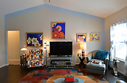 The living room features a group of paintings of flowers by Madison, Wisconsin artist Yukari. In her short career as an artist, Yukari only created ten acrylic paintings, and Sheridan and Rikki Glen own four of those ten. Sheridan and Rikki Glen are At Home in their Tanglewood subdivision home in Caseyville, IL on Wednesday January 16, 2019. <br /> Photo by Tim Vizer