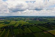 Nederland, Overijssel, Gemeente Twenterand, 30-06-2011; Landschap ten noorden Vriezenveen, links Vroomshoop, rechts Westerhaar-Vriezeenveensewijk. Voorbeeld van vroege ruilverkaveling (jaren '50). De oorspronkelijk (zeer) smalle en lange kavels, ontstaan door het ontginnen van veen, zijn samengevoegd tot grotere blokken en veelal is het kavelpatroon 90 graden gedraaid. De globale oorspronkelijke - onderliggende - structuur is deels nog herkenbaar..Naast de gedraaide verkalveling is verder kenmerkend de 'boerderijstraten', linten van boerderijen omgeven door singels van bomen (diagonaal in het midden)..Landscape north of Vriezenveen, an early example of land consolidation (50s)..The original (very) long and narrow lots, created by the extraction of peat, are merged into larger blocks and in most cases the plot pattern has been rotated 90 degrees  The original - underlying - structure is still partly visible..Further characteristic features are the 'farm roads' with farmhouses surrounded by belts of trees..luchtfoto (toeslag), aerial photo (additional fee required).copyright foto/photo Siebe Sw