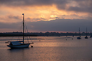 Moorings on the River Deben in the evening sunlight as the sun dips behind clouds