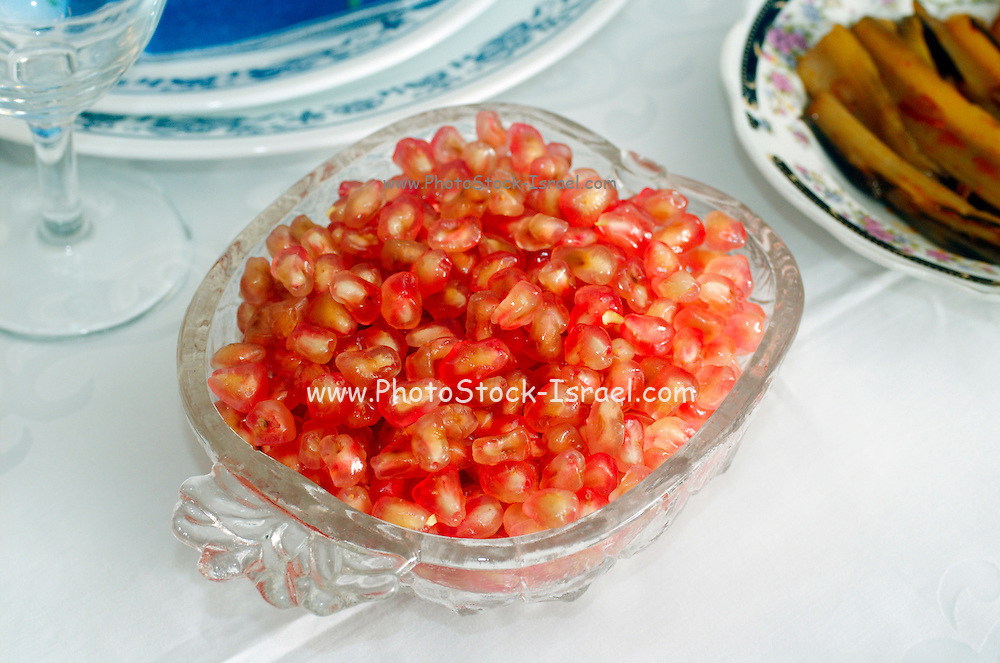 A dish of pomegranate seeds on the Table set for the Jewish feast of Rosh Hashana, the start of the new Jewish year, the pomegranate seeds symbolize plenty and many rights with the Lord
