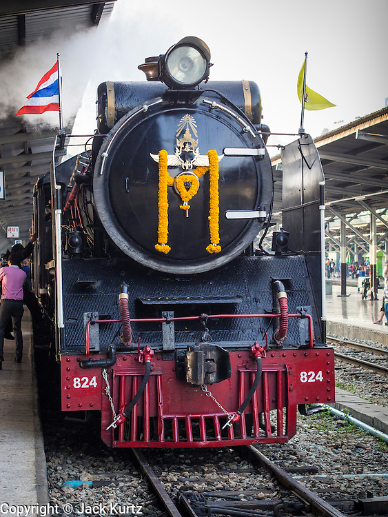 """05 DECEMBER 2013 - BANGKOK, THAILAND:  A special steam engine train leaves Hua Lamphong Train Station on the 86th birthday of Bhumibol Adulyadej, the King of Thailand. Dec. 5, the King's Birthday, is a national holiday in Thailand, and is also celebrated as the country's """"Fathers' Day."""" The State Railways of Thailand put on special trains to take people to the King's """"Summer Palace"""" in the oceanside community of Hua Hin where the King granted a public audience. There were also merit making ceremonies throughout the country.  Many people wear yellow on the King's Birthday because yellow is the color associated with his reign. As of 2013, he was the longest reigning monarch in the world.          PHOTO BY JACK KURTZ"""