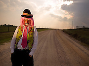 A clown dressed in bright neon clothing stands alone and sad with hands in pockets on a dirt road at sunset.