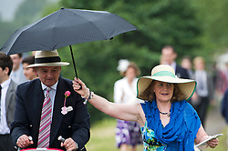 © London News Pictures. 03/07/2013.   Henley-on-Thames, UK.  A woman shelters her husband from the rain on Day one of Henley Royal Regatta on the River Thames at Henley-on-Thames, Oxfordshire on July 03, 2013. Photo credit: Ben Cawthra/LNP