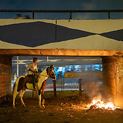 A horse rider approaches a fire. On the edge of the city, horses are kept under highway bridges at night while their owner sleeps nearby. The horses are used to pull horse carriage for tourists during the day.