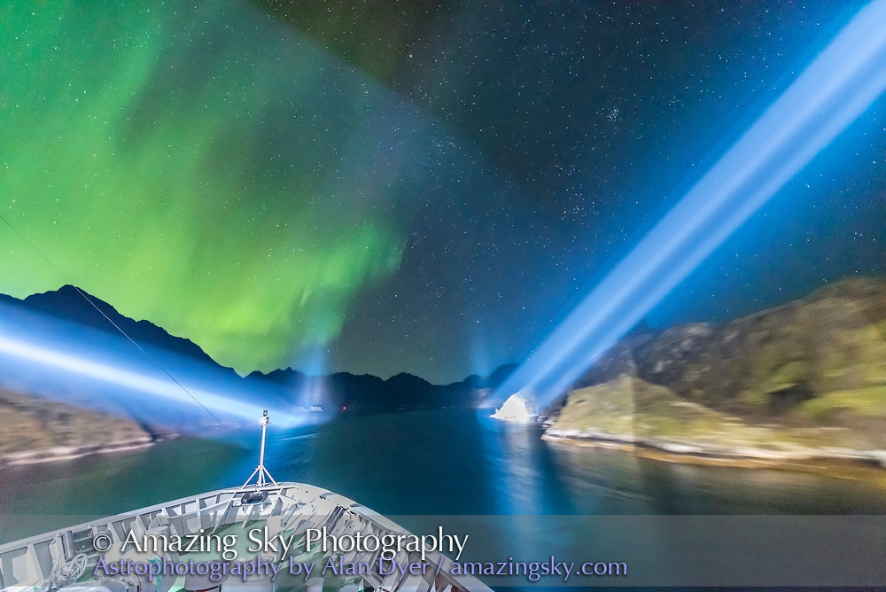The scene as the m/s Nordlys exits the narrow Trollfjorden fjord, with the ship's spotlights lighting the walls of the narrow fjord and with the aurora dancing. Ahead lies the winter sky with Taurus and the Pleiades rising. This was a magical moment indeed, one of the best of the Norway cruise. <br /> <br /> This is a single 0.8 sec exposure with the 14mm Sigma Art lens at f/1.8 and Nikon D750 at ISO 6400.
