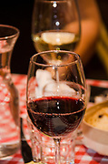 A glass of Red Wine at a table laden with snacks and finger foods
