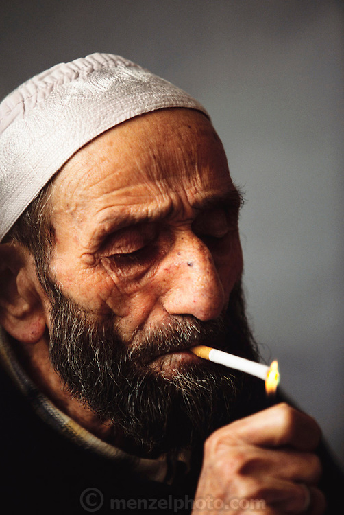 Chain-smoking Mehmet Çinar, 81, lights a cigarette in the small room he shares with his wife Emine, 78. He is bed ridden with lung-related maladies but says that smoking is not harmful. Golden Horn (or Haliç) area, Istanbul, Turkey.