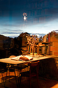 open book under lamp light reflecting in window with a dark evening or early morning sky