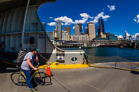 Bicyclists waiting to dock on the waterfront near Downtown Seattle after crossing Puget Sound from Bainbridge Island,  Washington USA.