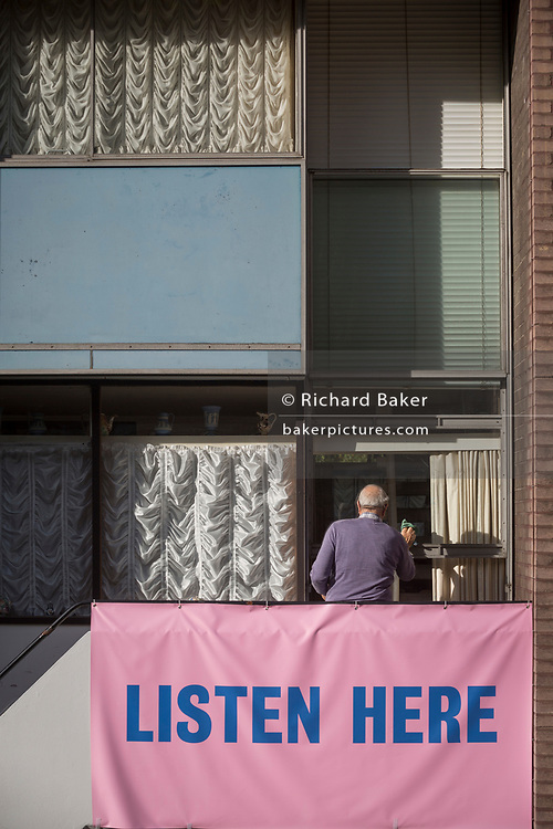 """A resident of Bowater House on the Golden Lane Estate cleans a window with a banner on the balcony protesting about the 10-storey luxury apartment development called The Denizen, a controversial building by Taylor Wimpey that locals say will dominate their view and block their daylight, on 30th October 2017, in London, England. Residents on the Estate have erected banners by artists Jeremy Deller and Elizabeth Price to picket the developers. Despite this, Wimpey say, """"We are one of the UK's largest residential developers. As a responsible developer we are committed to working with local people and communities."""""""