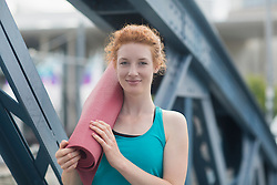 Portrait of a young woman standing with exercise mat in urban city, Freiburg im Breisgau, Baden-Wuerttemberg, Germany