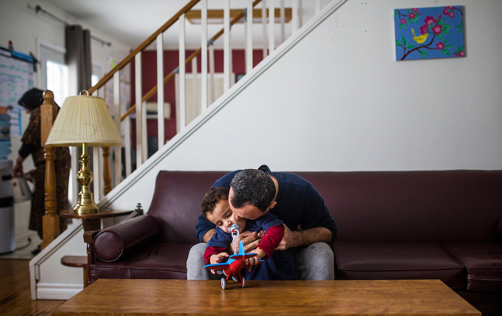 Syrian Refugee Abdel Malek Al Jasem holds his son Fadl inside their temporary home in Picton, Ontario, Canada, Wednesday January 20, 2016.   (Mark Blinch for the BBC)