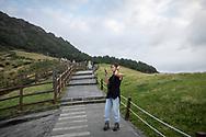 Jeju Island, South Korea - September 12, 2019: A South Korean woman visiting Jeju Island looks at her phone while visiting Seongsan Ilchulbong, an archetypal tuff cone and national landmark.
