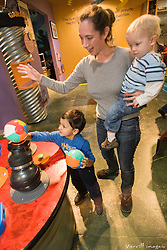 United States, Washington, Bellevue, KidsQuest Children's Museum, woman with two boys at Whoosh exhibit