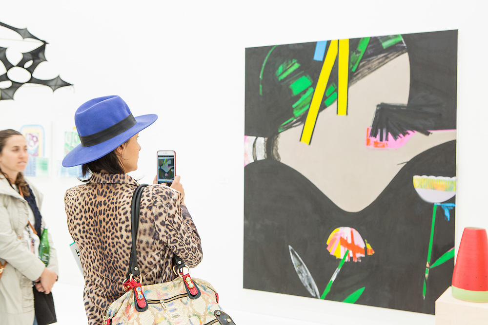"New York, NY - 6 May 2016. Frieze New York art fair. A woman  in a blue hat takes a photo of Ellen Berkenblit's oil ""Griffe"", in the Anton Kern Gallery booth."