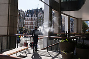 A vaping smoker exhales his vape smoke while standing in late-summer sunshine near Liverpool Street Station in the City of London, the capital's financial district, on 24th September 2021, in London, England.