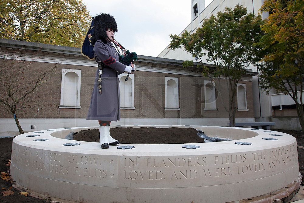 © Licensed to London News Pictures. 07/11/2013. London, UK. Piper Lance Corporal James Bell of F Company the Scots Guards plays his bagpipes on the centre piece of the 'Flanders Field Memorial Garden 1914-2014' at Wellington Barracks, London, today (07/11/2013) during the launch of a year-long initiative to fund the new garden. Located in the grounds of the Guards Museum, itself associated with the British Army's Guards regiments who have fought in Belgium on numerous occasions, the garden is set to be completed in 2014 using soil from World War One battlefields in Flanders, Belgium, to create a 'garden of remembrance'. Photo credit: Matt Cetti-Roberts/LNP