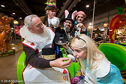 """Mr Martini's booth with the Mad Hatter, Alice, the White Rabbit and King of hearts in their Alice in Wonderland """"Through the Looking Glass"""" theme during the Motor Bike Expo. Verona, Italy. January 24, 2016.  Photography ©2016 Michael Lichter."""