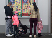 A family lining up outside of a shop during the second lockdown in England.