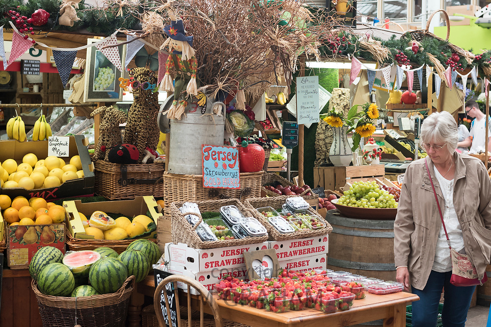 Fruit and other items on sale at St Helier Central Market in historic Victorian market hall, in Jersey, Channel Isles