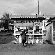 A lady shops at a small 'American fast food' kiosk situated on the main road running through the small Romanian town of  Copsa Mica, Transylvania, Romania. Copsa Mica was once described as the most polluted town in Europe. May 9, 2008  Photo Tim Clayton...Copsa Mica, a small industrial town deep in Transylvania, Romania, was described during the 1990s as the most polluted town in Europe with lead levels reaching were more than 1000 times the allowable International limits and life expectancy nine years shorter than the National average...The pollution was caused entirely by two factories, Carbosin produced black for dies and tires and closed in 1993 while Sometra, a nonferrous smelter is still operational today...The pollution was so bad sheep were black, covered in soot and health officials advised against eating livestock or vegetables and drinking the water or milk...The Communist rule of Nicolae Ceausescu is blamed for the widespread environmental degradation that left industrial parts of Romania in ecological disaster. Industry was situated in a way to concentrate pollution in small areas leaving the rest of the country relatively free of pollution.Copsa Mica in particular was left an environmental disaster...The pollution caused a direct affect on human health with widespread Lung disease, Impotency, the highest infant mortality rate in Europe, Lead poisoning andbehavioral problems...Fifteen years on since the closure of Carbosin in 1993, the factory skeleton remains as part of the towns bleak landscape, Unfinished communist style housing blocks still stand in the heart of the towns housing estate. The town's inhabitants arestill trying to recover from the long lasting effects of pollution...Recent survey's found the soil contained so much lead that it was 92 times above the permitted level; the vegetation had a lead content 22 times above the permitted level. While toxins have penetrated at least one meter (three feet) into the soil lea