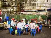 "06 NOVEMBER 2015 - YANGON, MYANMAR: Men eat and drink tea at an informal tea shop on a Yangon street. Some economists think Myanmar's informal economy is larger than the formal economy. Many people are self employed in cash only businesses like street food, occasional labor and day work, selling betel, or working out of portable street stalls, doing things like luggage repair. Despite reforms in Myanmar and the expansion of the economy, most people live on the informal economy. During a press conference this week, Burmese opposition leader Aung San Suu Kyi said, ""a great majority of our people remain as poor as ever.""    PHOTO BY JACK KURTZ"