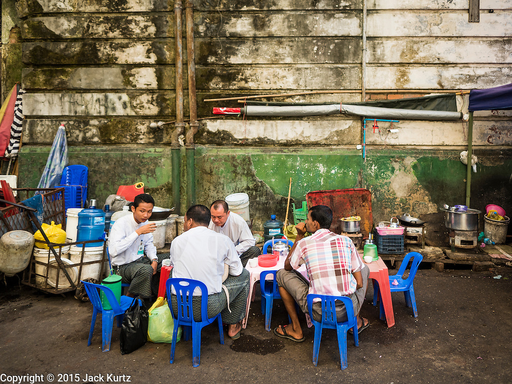 """06 NOVEMBER 2015 - YANGON, MYANMAR: Men eat and drink tea at an informal tea shop on a Yangon street. Some economists think Myanmar's informal economy is larger than the formal economy. Many people are self employed in cash only businesses like street food, occasional labor and day work, selling betel, or working out of portable street stalls, doing things like luggage repair. Despite reforms in Myanmar and the expansion of the economy, most people live on the informal economy. During a press conference this week, Burmese opposition leader Aung San Suu Kyi said, """"a great majority of our people remain as poor as ever.""""    PHOTO BY JACK KURTZ"""