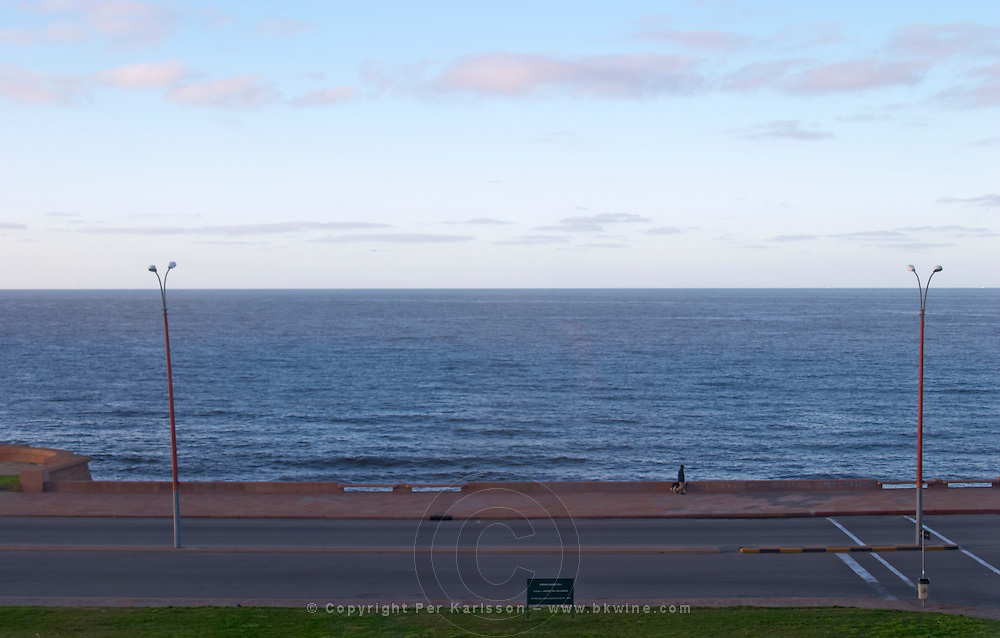 Coast line at dawn with horizon a man walking the dog, two lamp posts. At dawn. Empty street. Montevideo, Uruguay, South America