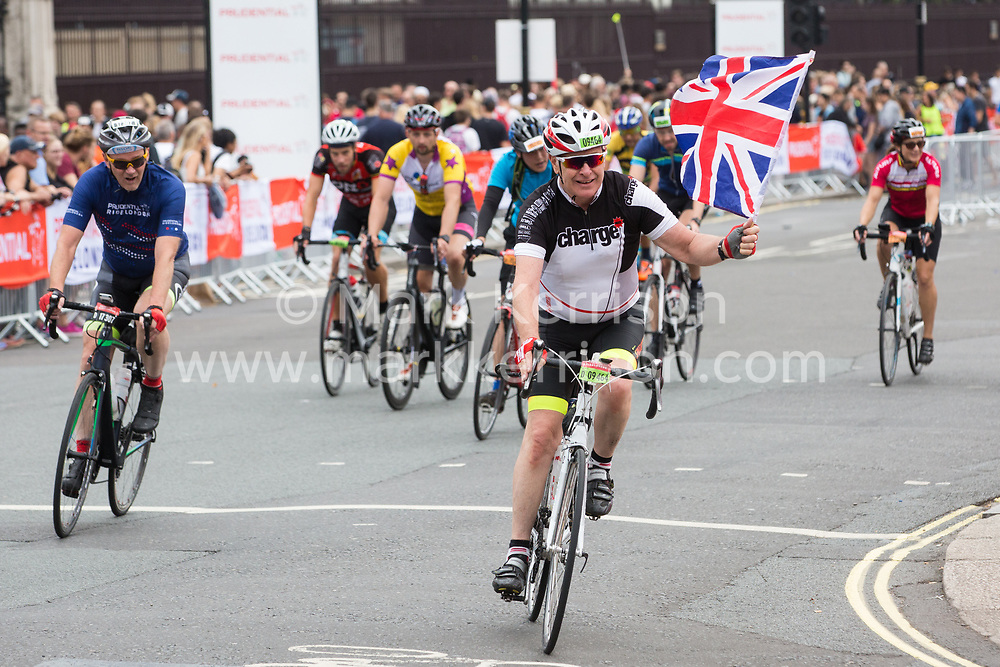 London, UK. 4 August, 2019. A rider holding a Union Jack approaches the finish for the Prudential RideLondon-Surrey 100 and 46 events in the Mall. Both events take place on traffic-free roads in London and Surrey, with the 100 event featuring leg-testing climbs on a route made famous by the London 2012 Olympics.