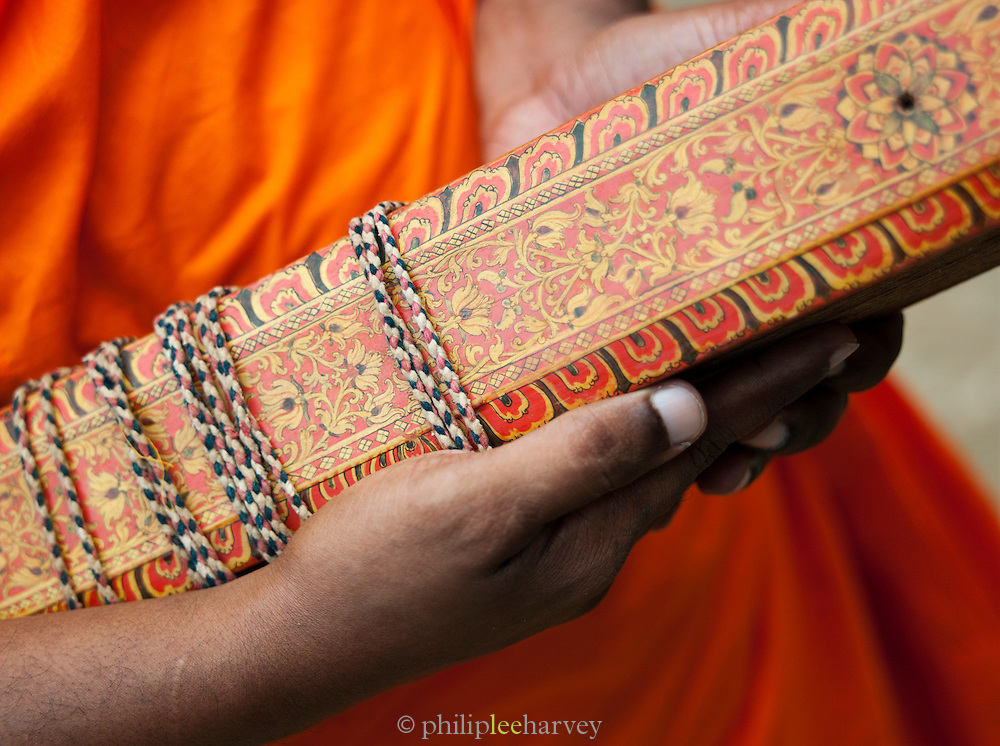 Buddhist monk holding religious texts, Mulkirigala Monastery, Sri Lanka