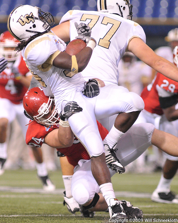 Dec 20, 2009; St. Petersburg, Fla., USA; Rutgers defensive tackle Scott Vallone (94) tackles UCF running back Brynn Harvey (34) during NCAA Football action in Rutgers' 45-24 victory over Central Florida in the St. Petersburg Bowl at Tropicana Field.