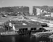 """Ackroyd_18973-1.""""LeBeck & Son. Aerials moving warehouse onto barge. August 2, 1974"""" (south Waterfront area south of the Hawthorne bridge. They are barging the entire 45,000 square feet Multnomah Plywood factory to its new home in St Helens.)"""