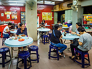 24 AUGUST 2018 - GEORGE TOWN, PENANG, MALAYSIA: Early morning shoppers have breakfast in a coffee shop next to Chowrasta Market in central George Town. Chowrasta Market was originally built in 1890 and is the older of two traditional markets in George Town. The original building was torn down and replaced with a modern building in 1961 and has been renovated several times since.     PHOTO BY JACK KURTZ