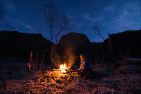Female hiker sits by campfire in frozen winter landscape at mountain camp, Vesterålen, Norway