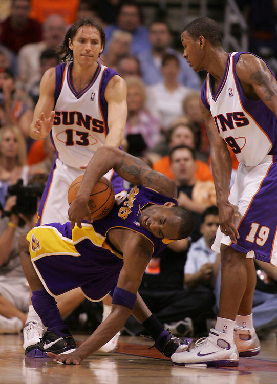 The Lakers' Kobe Bryant gets a hard foul by the Suns' Raja Bell as Steve Nash looks on during the second half of the Lakers 114-97 loss to the Phoenix Suns' in Game 5 of the Western Conference quarterfinals at U.S. Airways Arena in Phoenix, Ariz. Tuesday May 2, 2006.