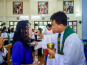19 NOVEMBER 2017 - HWAMBI, YANGON REGION, MYANMAR: Father JOHN LEE (right) serves communion at Sacred Heart's Catholic Church in Hwambi, about 90 minutes north of Yangon. Catholics in Myanmar are preparing for the visit of Pope Francis. He is coming to the Buddhist majority country November 27-30. There about 500,000 Catholics in Myanmar, about 1% of the population. Catholicism was originally brought to what is now Myanmar more than 500 years ago by Portuguese missionaries and traders.    PHOTO BY JACK KURTZ