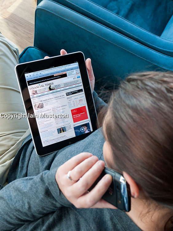 Woman using iPad computer tablet to read Financial Times newspaper in airport departure lounge
