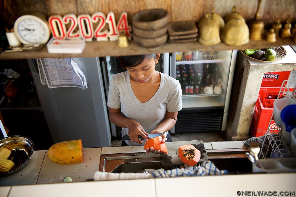 A waitress prepares fresh papaya at a cafe in Ubud, Bali, Indonesia.