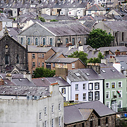 Rooftops of houses and buildings with their Welsh slate roof tiles as seen from one of the towers at Caernarfon Castle in northwest Wales. A castle originally stood on the site dating back to the late 11th century, but in the late 13th century King Edward I commissioned a new structure that stands to this day. It has distinctive towers and is one of the best preserved of the series of castles Edward I commissioned.