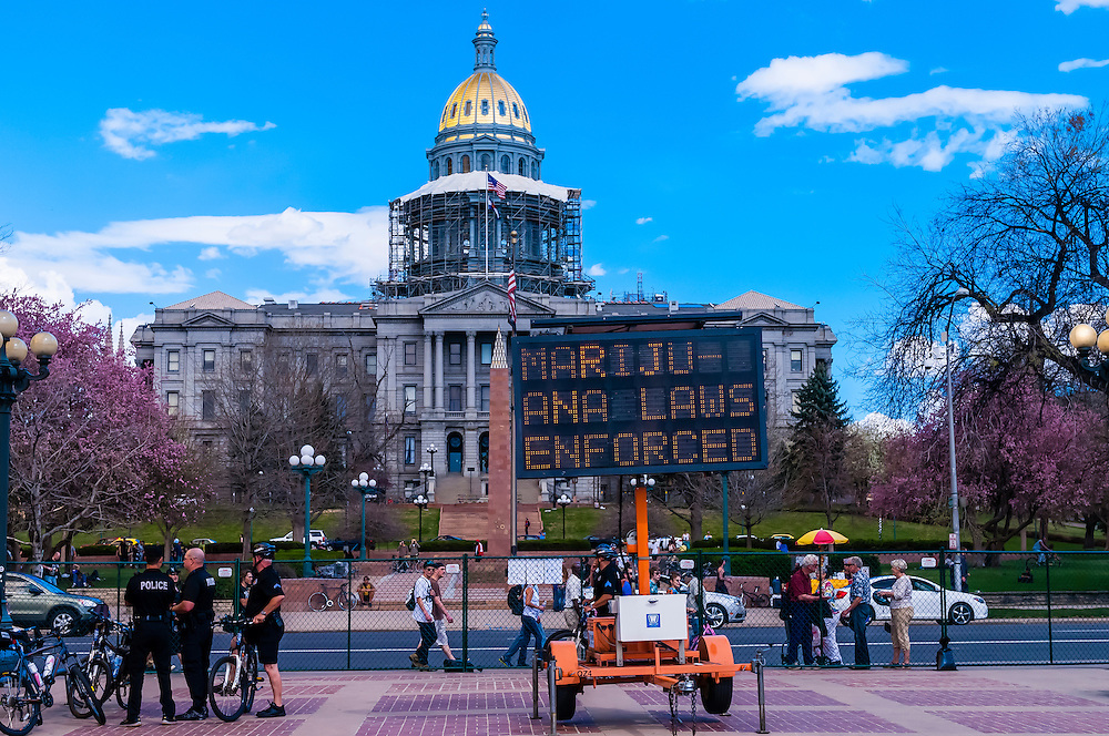 """Denver Police stand near one of the entrances (and electronic billboards stating """"Marijuana Laws Enforced"""" (with the Colorado State Capitol in back) to the 420 Cannabis Culture Music Festival, Civic Center Park, Downtown Denver, Colorado USA. This was the first 4/20 celebration since recreational pot became legal in Colorado January 1, 2014. A crowd of up to 80,000 people attended the event."""