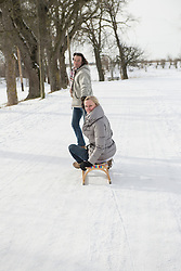 Man dragging woman on sledge in snow, Bavaria, Germany