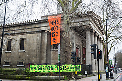 London, UK. 6th February, 2021. Banners in support of environmental activists from anti-HS2 campaign group HS2 Rebellion occupying tunnels beneath Euston Square Gardens hang from St Pancras Church. National Eviction Team bailiffs have been working for the past eleven days to remove the activists from the tunnels which were dug by them in order to seek to protect trees from felling in connection with the HS2 high-speed rail project.