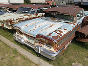 classic cars sitting in a junkyard