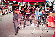 May 2 - BANGKOK, THAILAND: Thai police sit in the shade in Sala Daeng intersection in what used to be Red Shirt territory. The Red Shirts moved  their barricades in the Sala Daeng Intersection in Bangkok Sunday further away from King Chulalongkorn Memorial Hospital after a threat that the government would move them out if they didn't move themselves. The move gave people full access to the hospital. The stand off between the Red Shirts and the government enters its third month in May. The Red Shirts continue to call for Thai Prime Minister Abhisit Vejjajiva to step down and dissolve parliament and demand the return of ousted Prime Minister Thaksin Shinawatra.   PHOTO BY JACK KURTZ