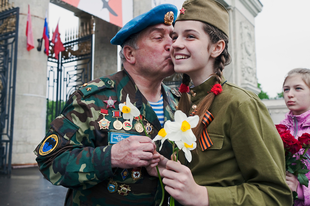 Moscow, Russia, 09/05/2012..A parachute regiment veteran kisses a girl in Soviet era uniform while she give him flowers as Russian World War Two veterans and well-wishers gather in Gorky Park during the countrys annual Victory Day celebrations.